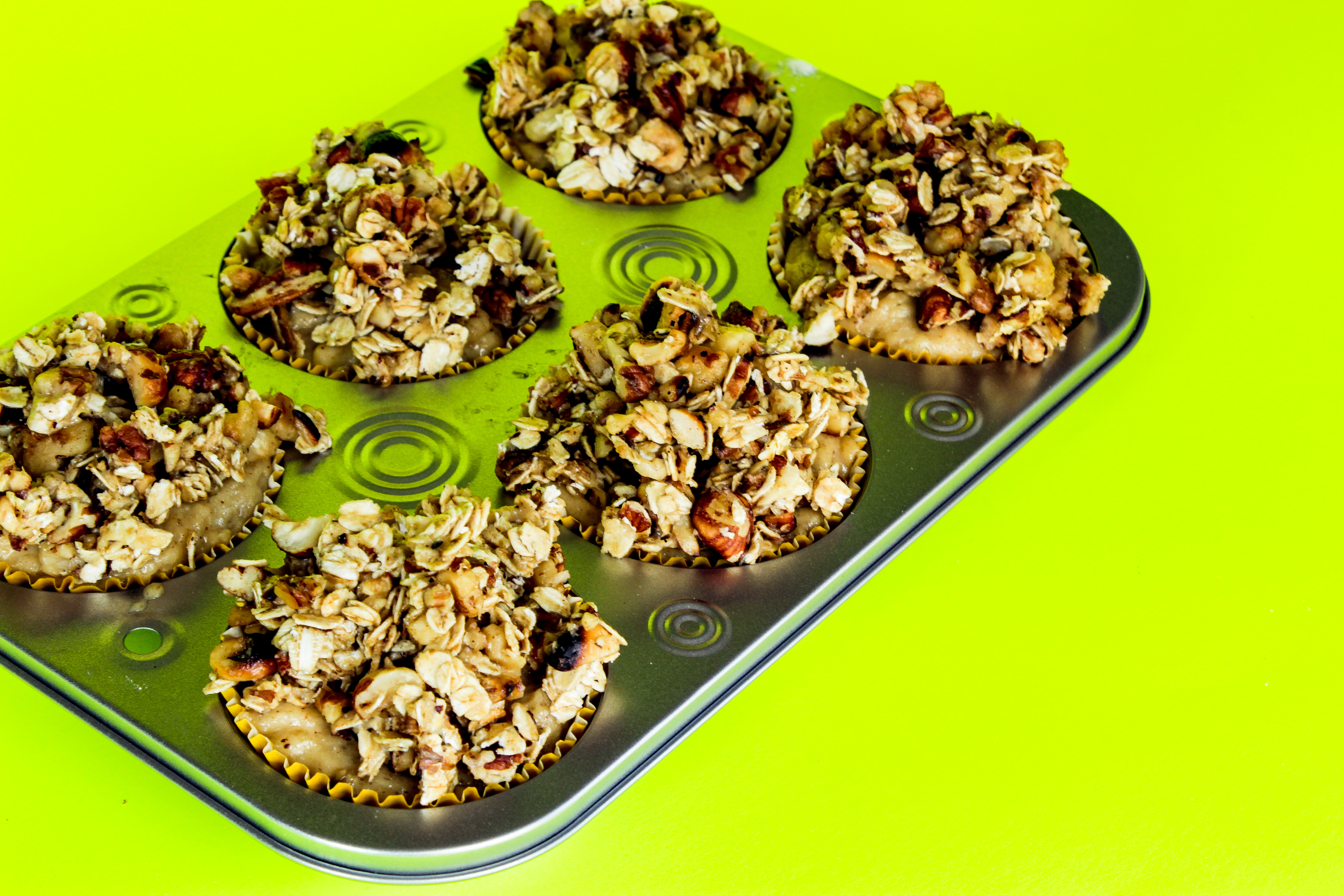 Batter of Brown Butter Banana Bread with Oatmeal and Nuts topping in a muffin pan.